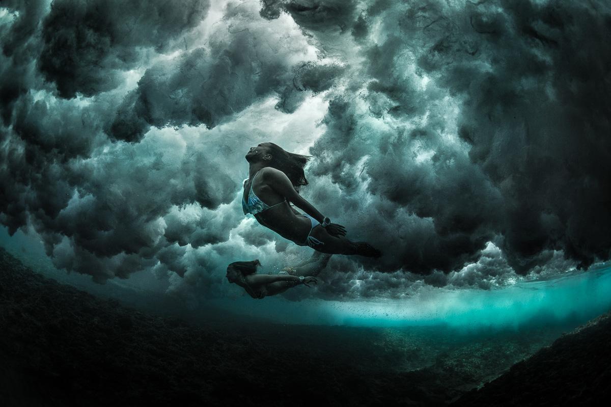 mermaids diving under waves